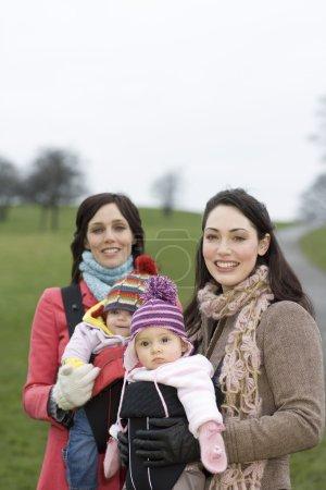 Photo pour Deux mères avec des bébés dans des porte-bébés dans le parc - image libre de droit