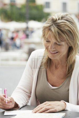 Woman tourist signing Postcard