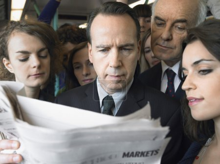 Businessman reading newspaper in train