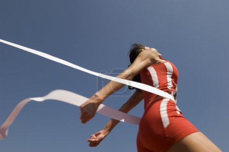 Photo for Young female athlete crossing finish line against clear blue sky - Royalty Free Image