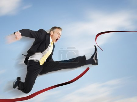Business man jumping through red tape