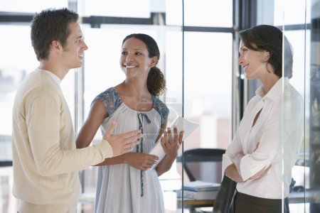 Photo for Three office workers standing in office talking. - Royalty Free Image