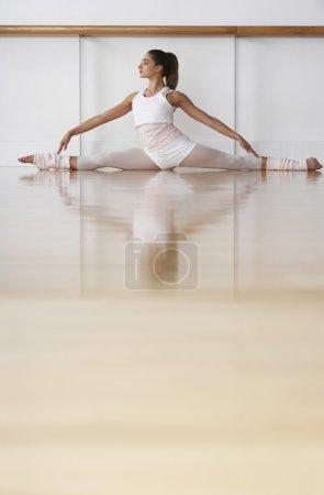 Ballerina doing split in rehearsal room