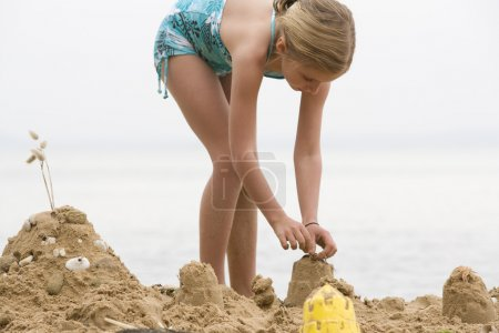 girl building sand castle