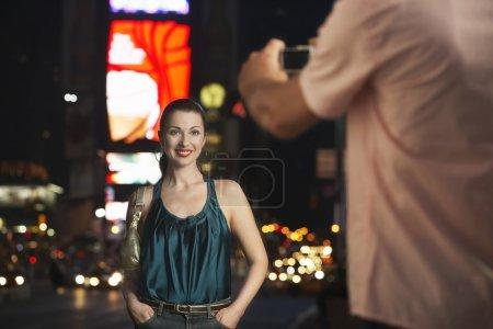 Photo pour Homme Photographier femme élégante à Times Square la nuit - image libre de droit