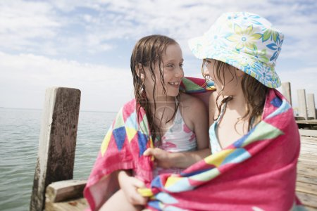 girls with in towel on wooden jetty