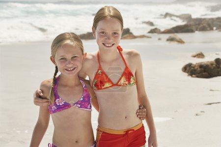 Two girls (7-9 10-12) posing on beach, portrait...