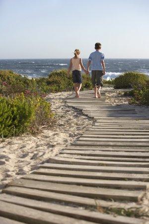 Boy and girl along boardwalk toward sea