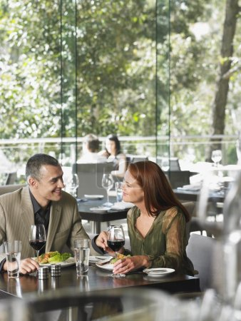 Couple talking over wine at bar