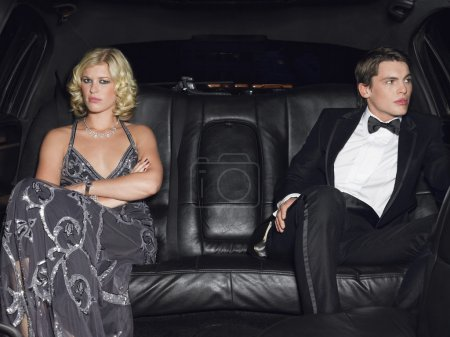 Photo for Couple in evening wear in back of car - Royalty Free Image
