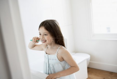 Photo for Girl Brushing Teeth in bathroom - Royalty Free Image