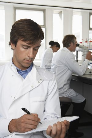 Lab Worker Writing on Notepad
