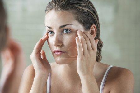 Photo pour Appliquer la crème pour le visage de femme - image libre de droit