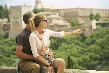 Photo for Tourist Couple sitting on Wall in Granada Spain looking and pointing at view - Royalty Free Image