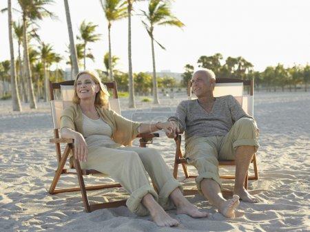 Photo pour Toute la longueur de l'heureux couple de personnes âgées vous détendre sur les transats à la plage tropicale - image libre de droit