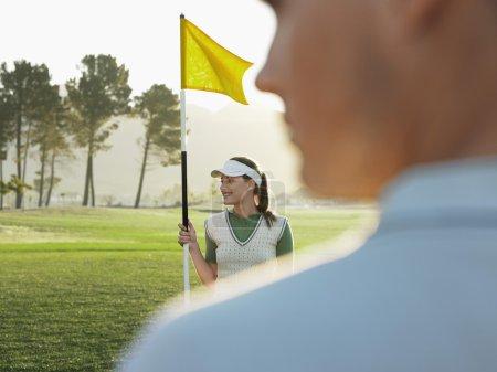 Golfer holding flag