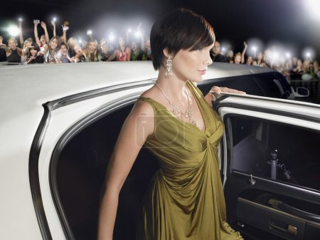 Photo for Woman in evening wear getting out of limousine in front of fans and paparazzi - Royalty Free Image