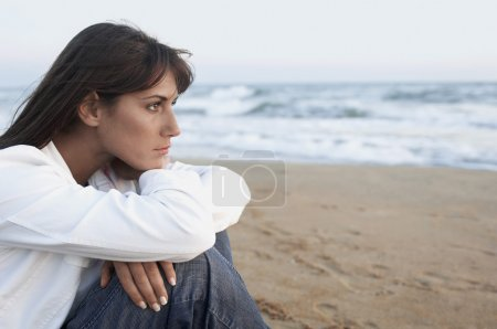 Photo for Pensive Woman on the Beach looking out to sea side view close up - Royalty Free Image