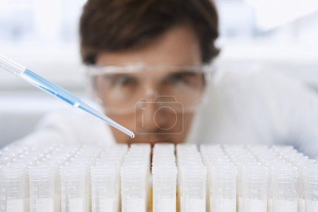 Male lab worker adding drops to test tubes