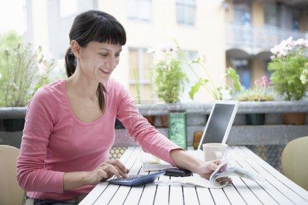Photo pour Femme d'affaires dans le calcul de t-shirt rose dans le jardin de ville - image libre de droit