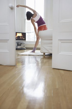Woman exercising and watching television