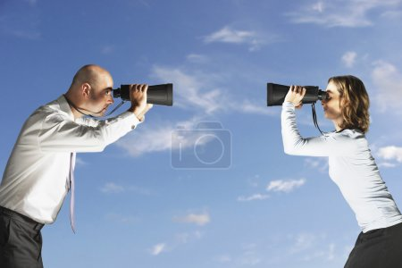 Photo for Businesspeople Holding BinocularsBusiness colleagues looking at each other through large binoculars outside profile - Royalty Free Image