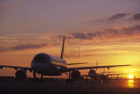 Photo pour Avions assis sur le tarmac au coucher du soleil - image libre de droit