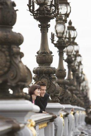 Couple looking over bridge
