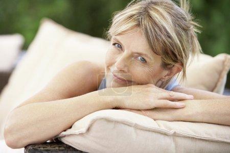 Photo pour Femme d'âge moyen assis sur le canapé dans le jardin portrait - image libre de droit