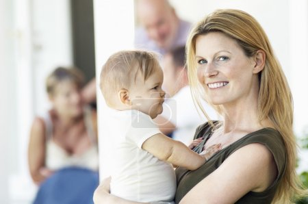 Photo for Mother holding baby on porch with grandparents behind - Royalty Free Image