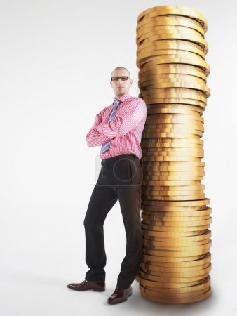 Man in glasses leaning against pile of coins