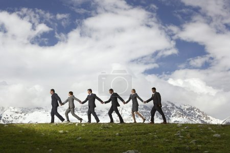 Photo for Business People Holding Hands and Walking through mountains side view - Royalty Free Image