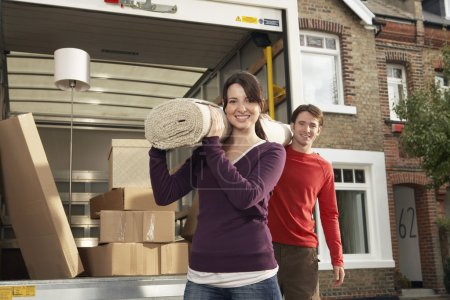 Photo for Portrait of happy young couple carrying rolled carpet by moving van - Royalty Free Image