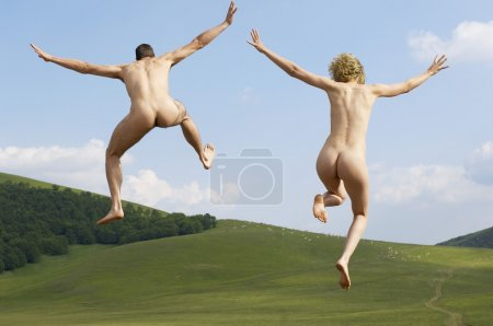 Naked couple jumping in field