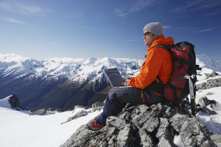 Mountain climber using laptop