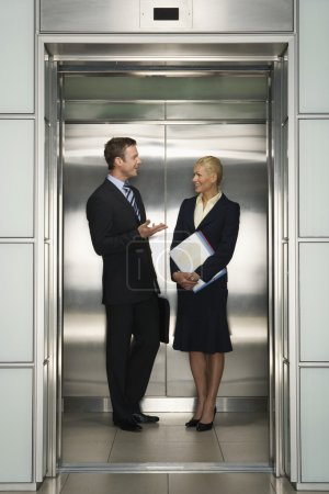 Businesspeople Talking in Elevator...