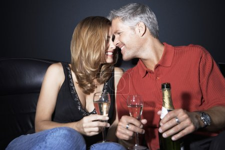 Couple with champagne flutes rubbing noses