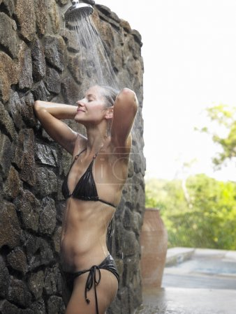 woman in black bikini taking shower
