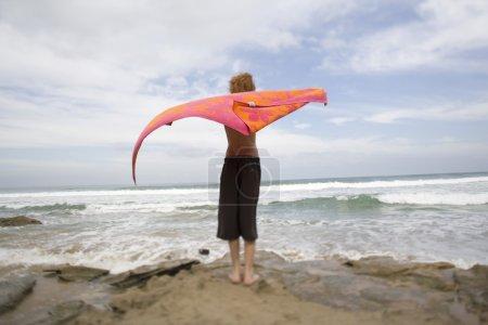 Photo pour Garçon debout sur la plage à bras ouverts, vue arrière - image libre de droit