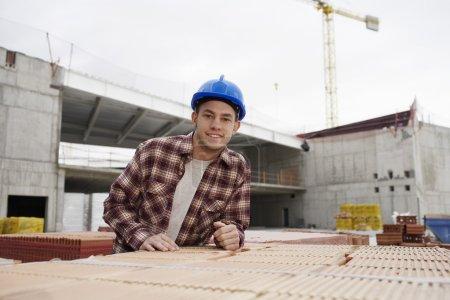 Photo pour Jeune ouvrier de la construction sur chantier - image libre de droit