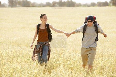 Hiking couple walking through field
