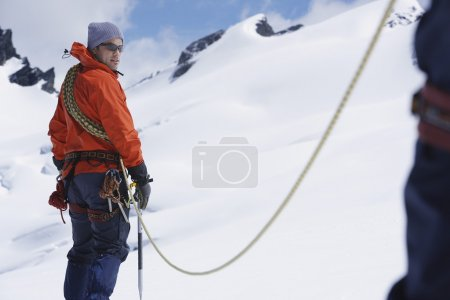 Hikers joined by safety line in snowy mountains