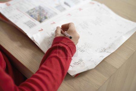 Photo pour Fille faire des devoirs sur la table avec cahier d'exercices - image libre de droit