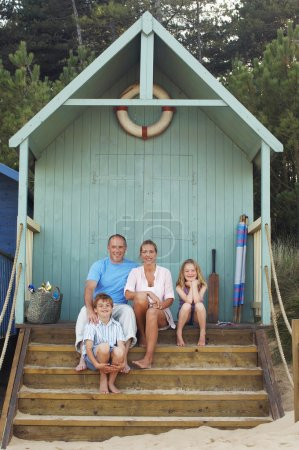 Family sitting in beach hut