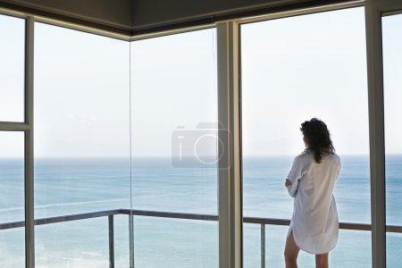 Woman Looking Through Window at Ocean