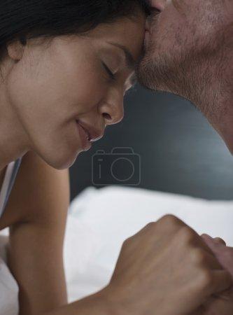 man kissing on female forehead