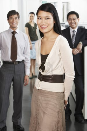 Photo pour Femme debout devant ses collègues dans le portrait de bureau - image libre de droit