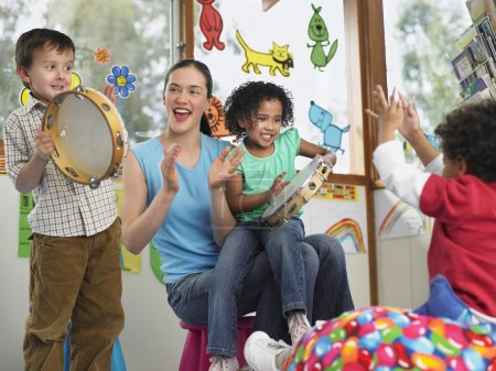 Photo for Children with teacher playing music in classroom - Royalty Free Image