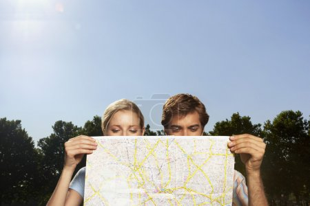 Vacationing couple looking at large map