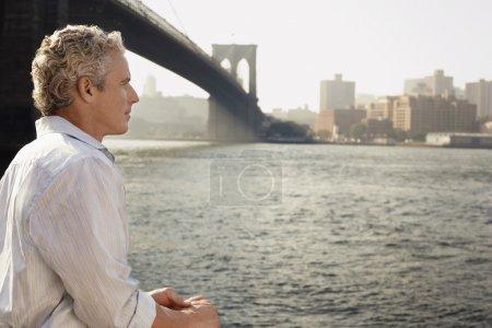 Man looking at river by Brooklyn Bridge